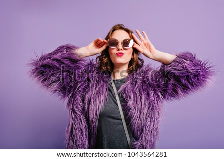 Lovable short-haired woman in stylish purple coat expressing happy emotions. Pretty girl with kissing face having fun on photoshoot in new soft jacket.