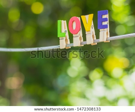 LOVE alphabet hang on sling with beautiful blurred bokeh background of green leaf. Simple and minimal vintage style of love photo concept and wallpaper. Copy space for text. Love is all around.