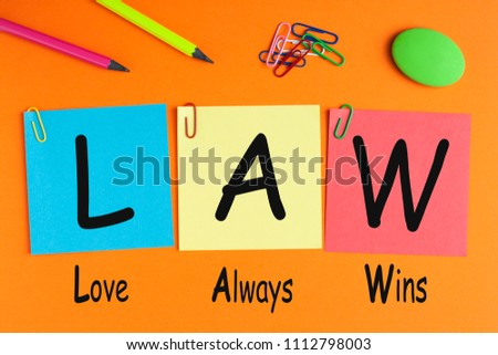 Love Always Wins- LAW written on written on color notes with and office supplies. #1112798003
