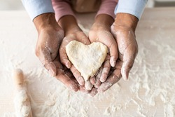 Love And Care Concept. Closeup above top view of unrecognizable african american man and girl baking cake in the kitchen and holding dough in heart shape in hands, dad and daughter cooking together