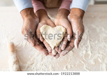 Love And Care Concept. Closeup above top view of unrecognizable african american man and girl baking cake in the kitchen and holding dough in heart shape in hands, dad and daughter cooking together Stock foto ©