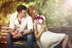 Love and celebrate concept. Young beautiful couple sitting in the park and man proposing woman.