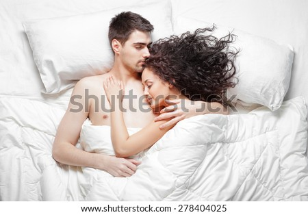 Love and comfort. Overhead of beautiful young couple lying on the bed sleeping and hugging. Top view.