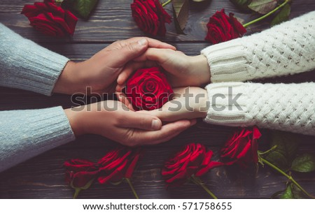 Love and family concept, male and female hands with red roses