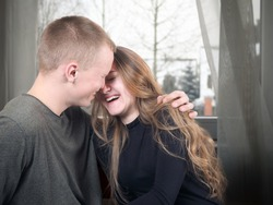 Love and happiness in the relationship of a young couple in love. The young man and girl laugh, sincere feelings of first love
