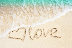 Love and heart symbol handwritten on tropical beach with soft wave on background