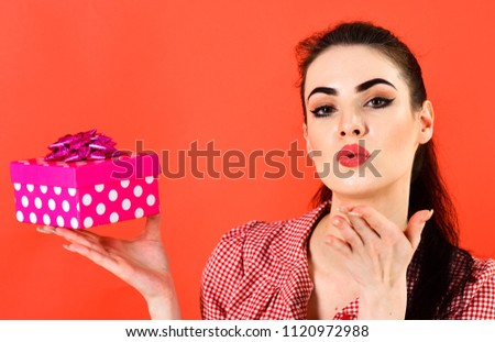Love and kiss. Girl and air kiss, make up, pink pack. Woman in stylish dress holds present. Lady with gift isolated on red background. Womans day, Christmas, shopping, New Year, Black Friday concept. #1120972988