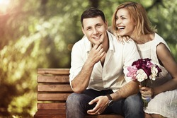 Love and marriage concept. Young attractive cheerful couple in the park and smiling. Woman responded to a marriage proposal.