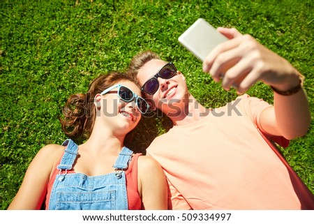 love and people concept - happy teenage couple in sunglasses lying on grass and taking selfie on smartphone at summer