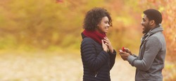 Love and relationship concept. Romantic man proposing to woman in autumn park, free space