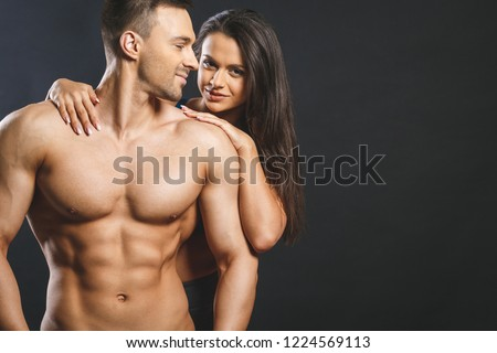 Love and sex concept - female hands touching muscular man isolated over grey background. Sexy fit couple, posing on a dark blackground.