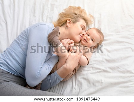 Love and tenderness, motherhood concept. Loving blonde mother caressing her cute baby boy, lying together on bed, top view. Young caucasian woman bonding with little kid at home, copy space