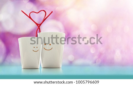 Love and Valentines Day Concept. Happy Lover Coffee Cup with smiley face and Straw in Heart Shape, Happiness and Romantic Couple, Colorful Pastel Bokeh as background #1005796609