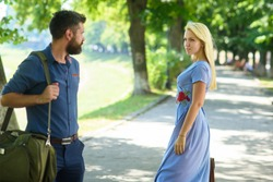 Love at first sight concept. Man and woman likes each other. Casual encounter, meet on sunny summer day, nature background, defocused. Man with beard and blonde girl stopped to get acquainted.