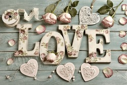 love background with vintage style letters ,hearts and roses lying on wooden planks