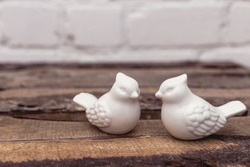 Love ceramics porcelain white birds on brown wooden and white bricked background. Vintage shabby chic style. Soft warm tender feelings.