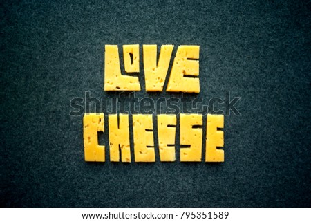 Love Cheese text word on dark background. Carve yellow cheddar into letters. Cheese Typography. Food lettering