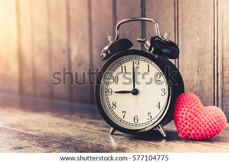 Love clock vintage tone timed 9 o'clock, Time of sweet loving past memories story on the old wood background. #577104775