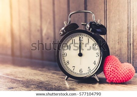 Love clock vintage tone timed 12 o'clock, Time of sweet loving past memories story on the old wood background. #577104790