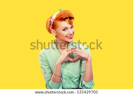 Love. Closeup portrait smiling happy pin up woman making heart sign symbol with hands isolated yellow wall background. Positive human emotion expression feeling life perception attitude body language