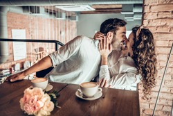 Love concept. Beautiful romantic couple playfully kissing while sitting in cafe.