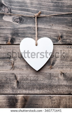 Love concept. Heart hanging on a string, shot on wooden background #360771641