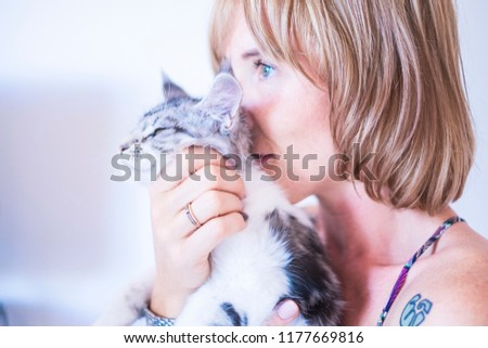 love concept with beautiful woman and sweet grey cats hugging and staying together in friendship. best friend lovely feline like perfect companion at home