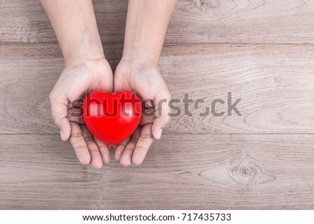 Love Concept : Woman hands holding red heart on brown wooden table background. Free space for text #717435733