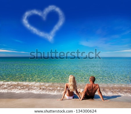 love concept - young couple on sea beach look at cloud heart at sky
