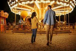 Love couple at the carousel, night amusement park