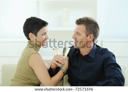 Love couple clinking champagne glasses at home on sofa. Smiling and looking at each other.?