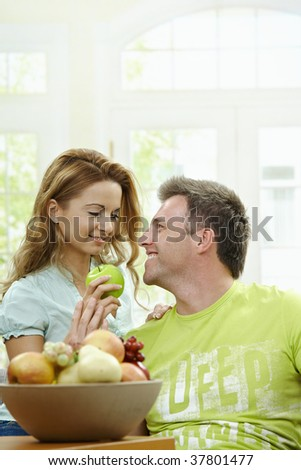 Love couple having breakfast together. Woman giving apple to her boyfriend.