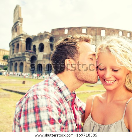Love - Couple Kissing Having Fun In Rome By The Colosseum. Romantic Tourists On Holidays Vacation Travel And Man Kissing Woman On Cheek. Beautiful Blonde Girl And Guy In 20s. Coliseum, Rome, Italy.