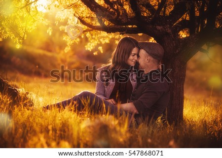 Love couple sitting under a tree in the colorful spring garden at sunset #547868071