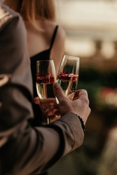 Love couple staying together and holding glasses with sparkling champagne and red heart shaped confetti. The concept of wedding, lovers day. Happy Valentines day celebration concept. Close up