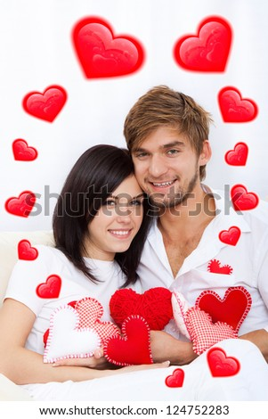 love couple valentine day heart shape, holding lot of red valentine's heart together sitting on couch at home, excited happy smile, hug, concept hearts flying around
