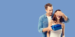 Love, dating, celebrating, lovers concept - happy amorous couple with blue gift box. Blue color background. Copy space for some text.