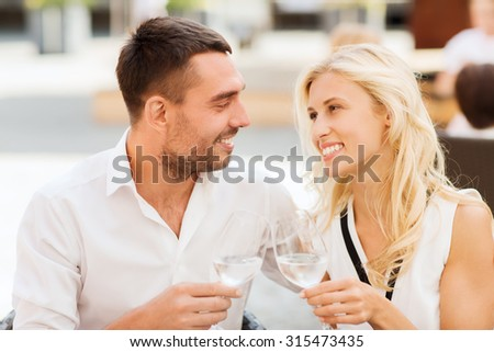 love, dating, people and holidays concept - smiling couple clinking glasses and looking to each other at restaurant lounge or terrace #315473435