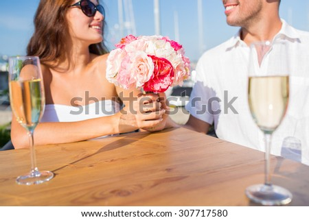 love, dating, people and holidays concept - smiling couple with bunch of flowers and champagne glasses and looking to each other at cafe