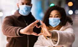 Love During Pandemic Concept. Portrait of african american couple wearing medical face masks making heart shape with hands walking together in the evening, selective focus. Connection And Support