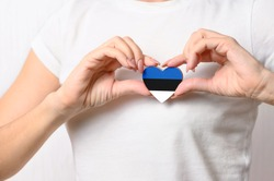 Love Estonia. The girl holds a heart in the form of the flag of Estonia on her chest. Estonian concept of patriotism