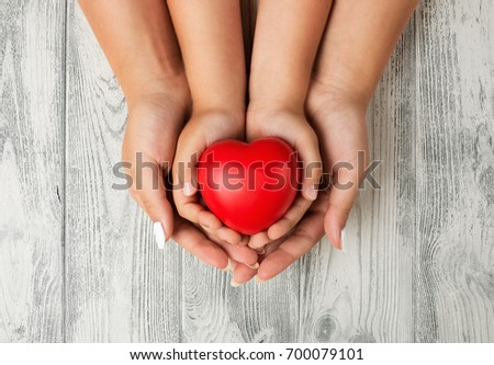 Love, family concept. Close up of mother and children hands holding red rubber heart together  #700079101