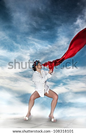 Love Flag/Pretty girl holding the red satin material flying in the wind. She is wearing curlers, white shirt and heels. Sky background