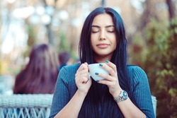 Love for coffee. Portrait of cute girl drinking enjoying her tea on the balcony over outside terrace with green bush background, wearing blue grey blouse and having breakfast, with pleasure relaxing