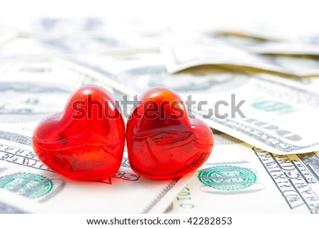 Love for money concept. Two glass hearts on dollar background.