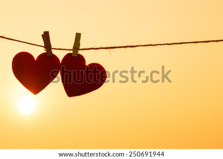 Love for Valentine's day - Two red hearts hung on the rope together with sunset silhouette