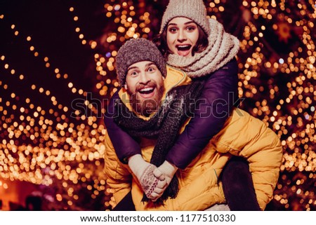 Love forever. Funky mood. Young handsome red bearded boyfriend is piggy backing his cute lover, wearing winter warm outfits, behind them are christmas illuminations