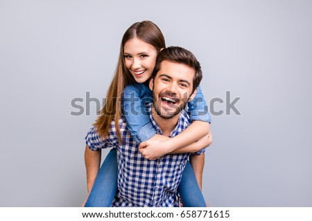 Love forever. Young brunete handsome bearded boyfriend is piggy backing his cute lover, wearing casual clothes, on pure background