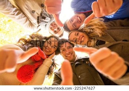 love, friendship, gesture, season and people concept - group of smiling men and women showing thums up in autumn park