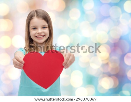 love, happiness, charity, children and people concept - smiling little girl giving red heart over blue holidays lights background